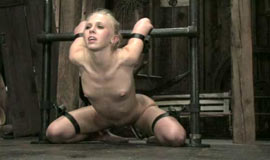 Blonde in bondage kneeling on the floor in trammels
